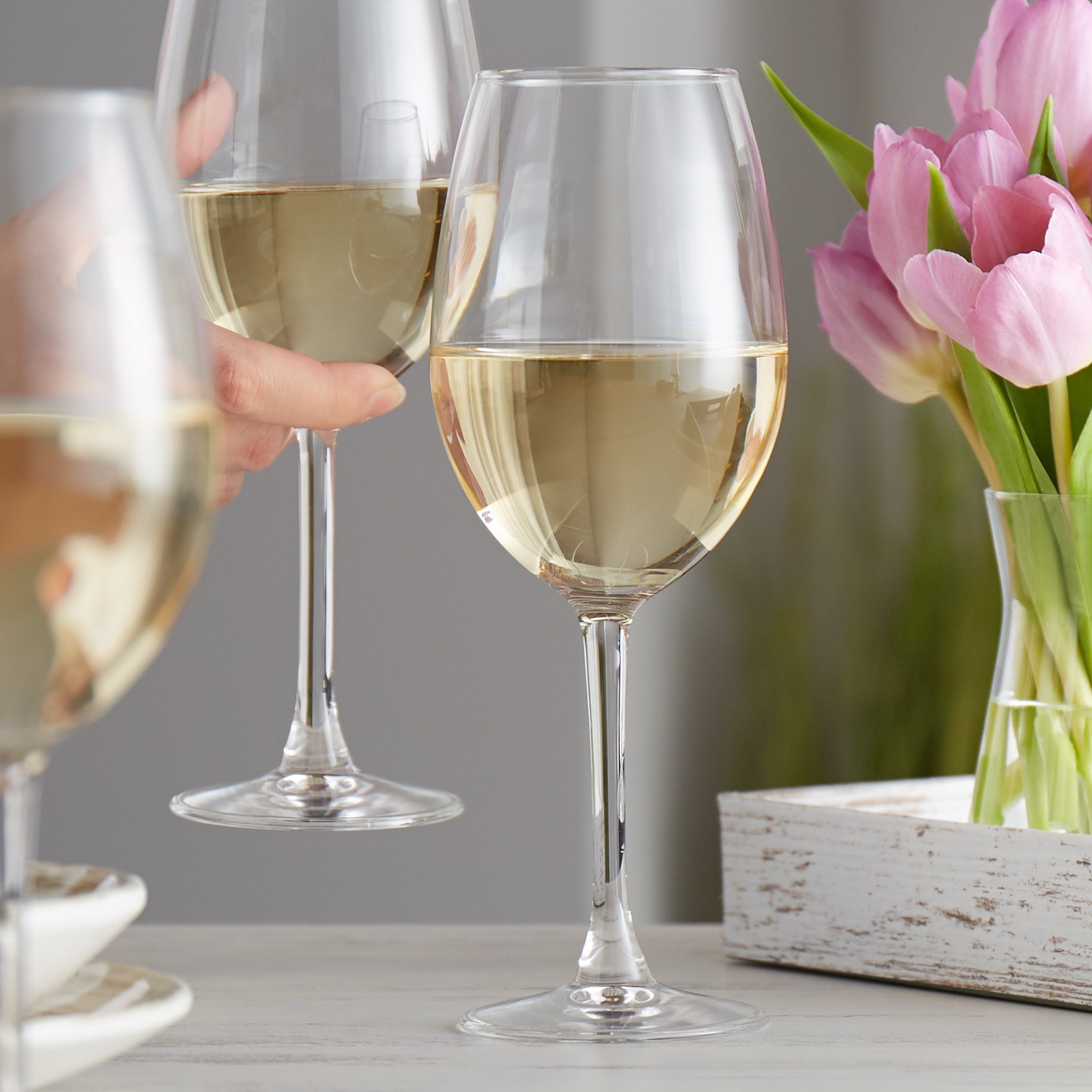 White wine glass filled with sauvignon blanc on an elegant table with tulips in the background
