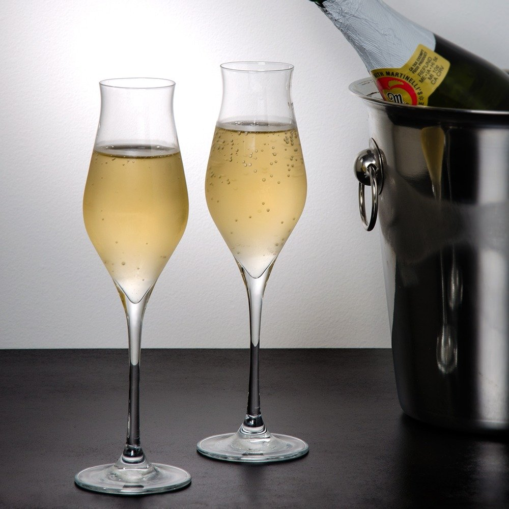 Two tulip wine glasses filled with sparkling wine in front of a stainless steel wine cooler
