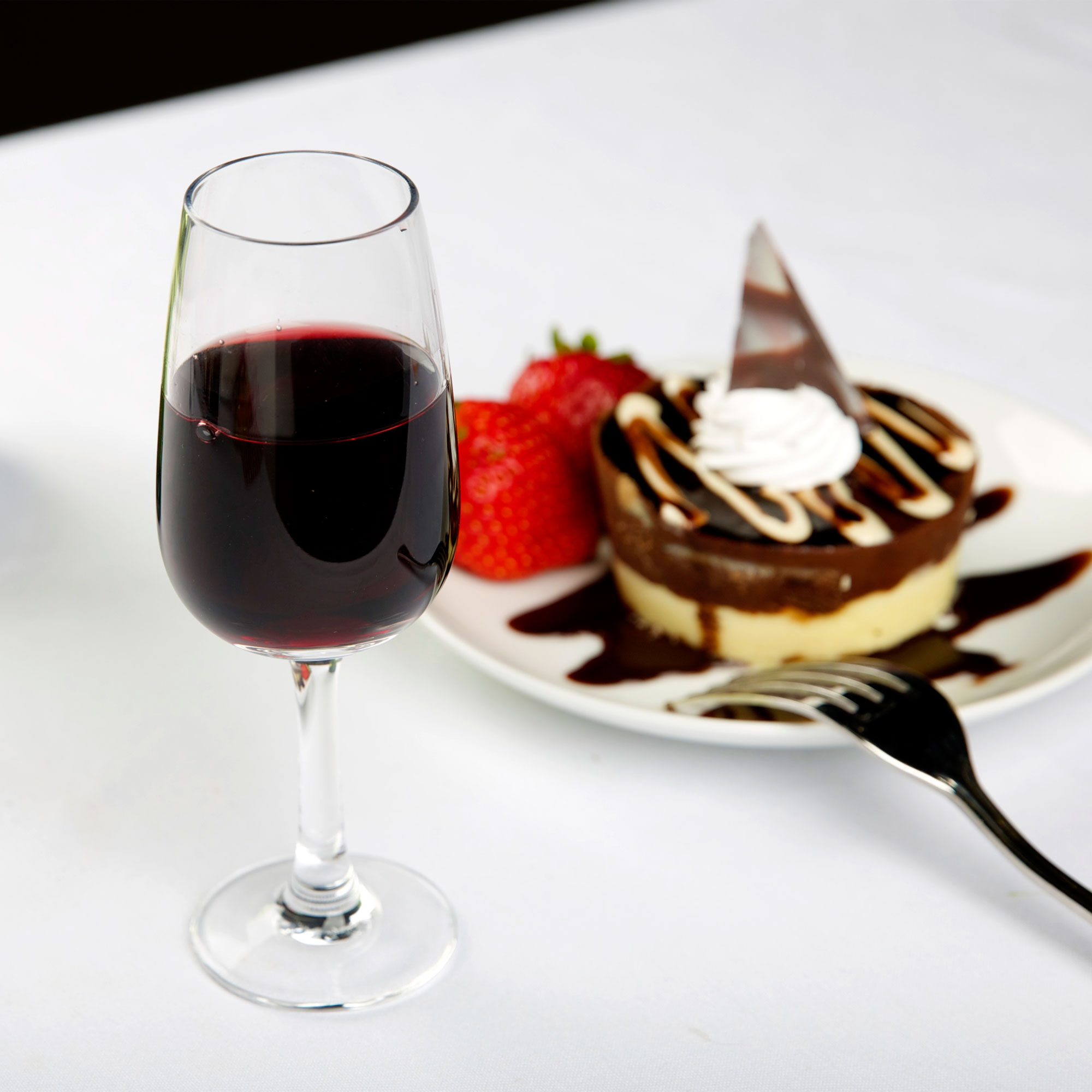 Dessert wine glass filled with port in front of an elegant dessert, complete with fresh strawberries