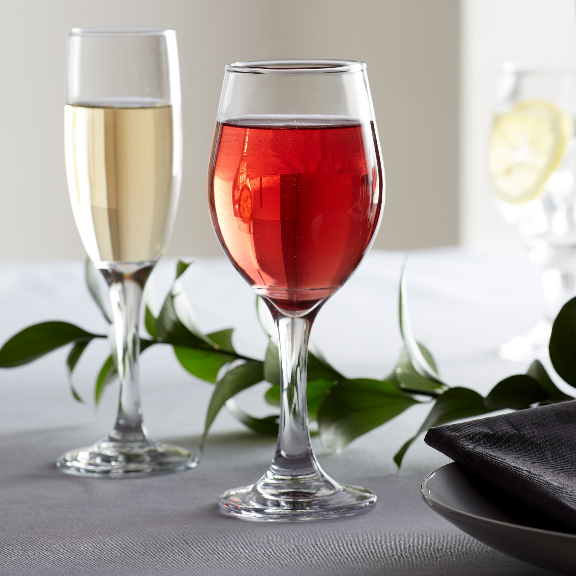 Two stemmed wine glasses filled with wine on an elegant table