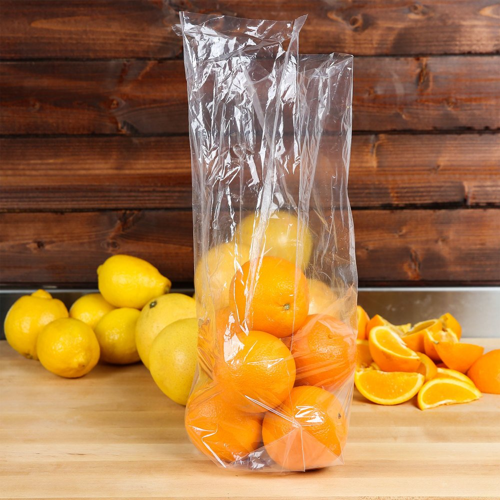 Oranges piled in a plastic bag with lemons and sliced oranges behind it