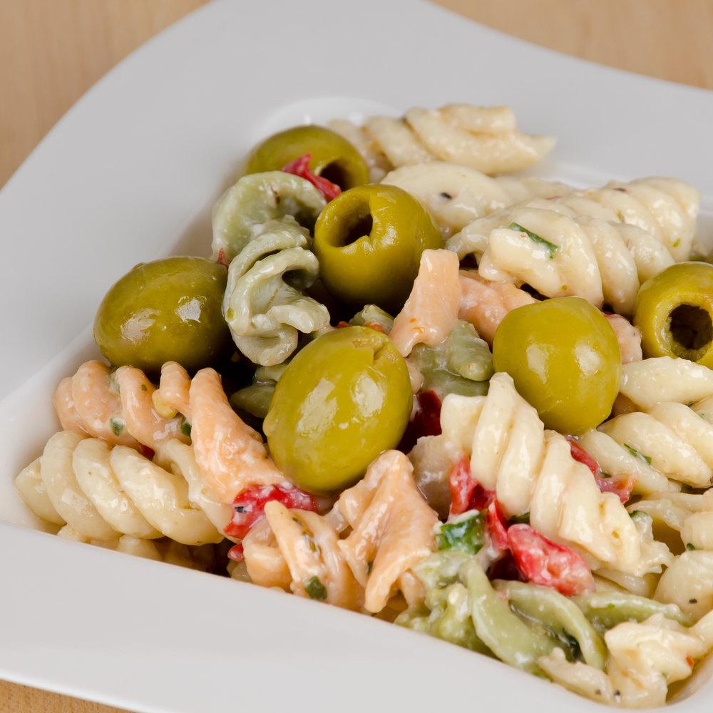 Green manzanilla olives in a bowl of pasta salad