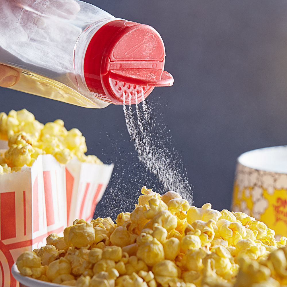 clear container with red lid pouring white popcorn salt onto a yellow pile on popcorn with bags of p