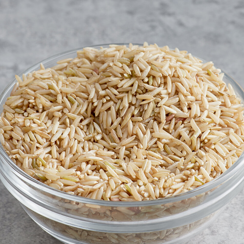Clear bowl full of brown basmati rice on a gray surface