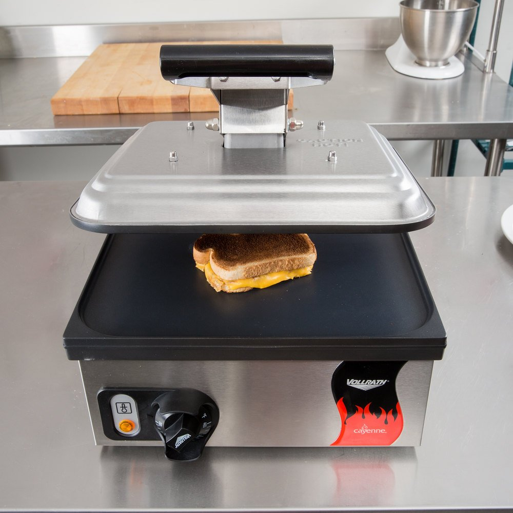 Vollrath single panini grill with non-stick plates, sitting on a counter and pressing a grilled cheese sandwich