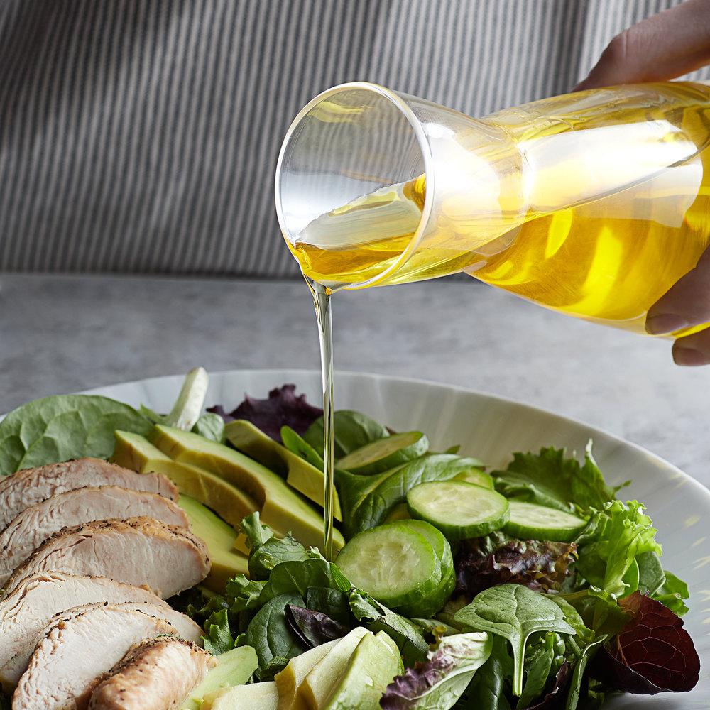 Person pouring avocado oil onto a salad
