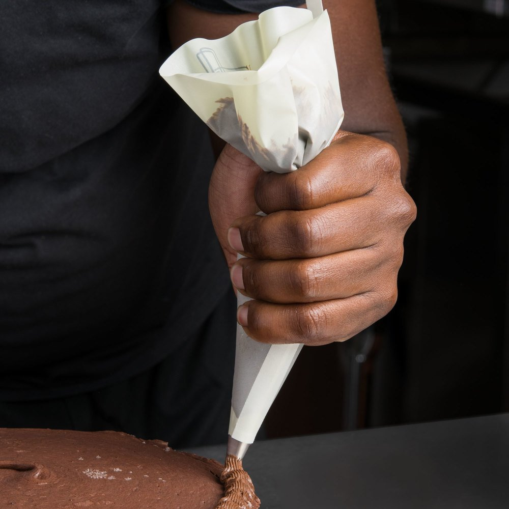 Baker using a nylon pastry bag to decorate a cake