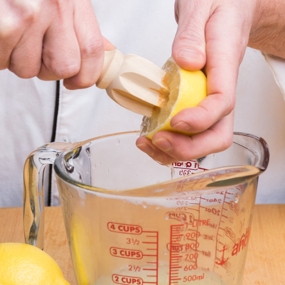 Chef using a wooden reamer to juice half of a lemon into a glass measuring cup