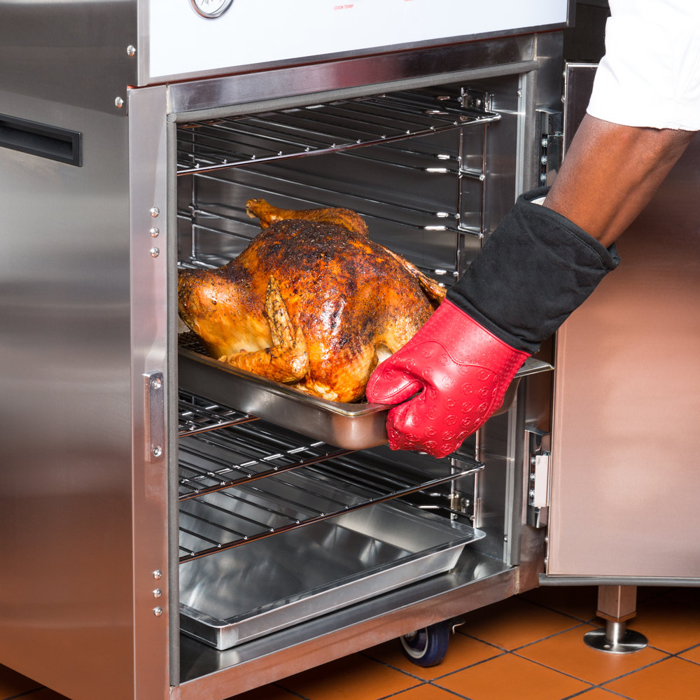 Arm pulling roasted turkey from Cooking Performance Group CHSP2 SlowPro stacked cook and hold oven