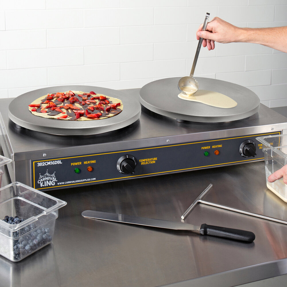 Dual Crepe maker with two cooking crepes next to a spatula and t-spreader.