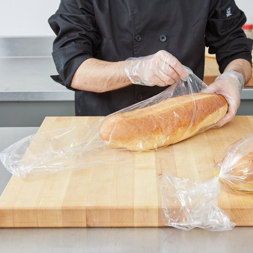 Loaf of bread being placed in plastic food bag on wood butcher block