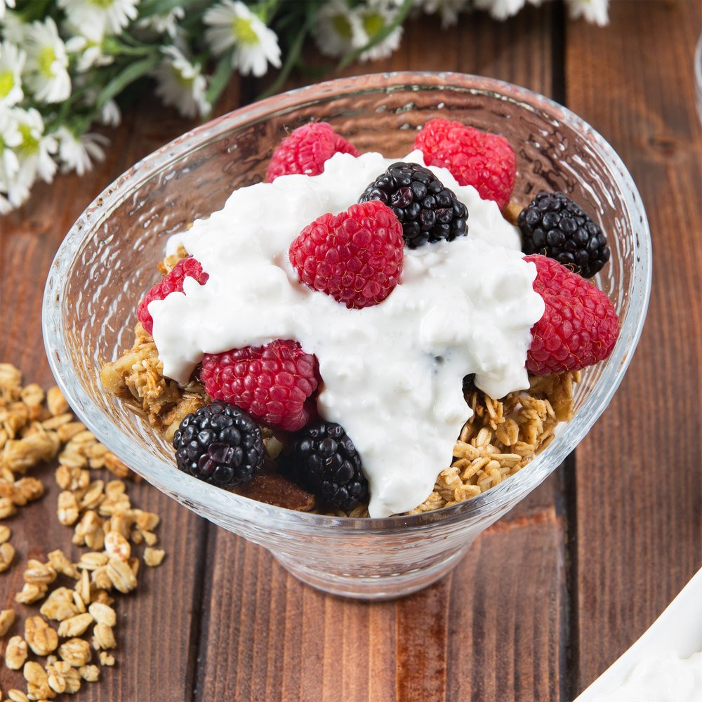 Cottage cheese in a modern glass serving bowl, spooned over granola, blackberries, and raspberries