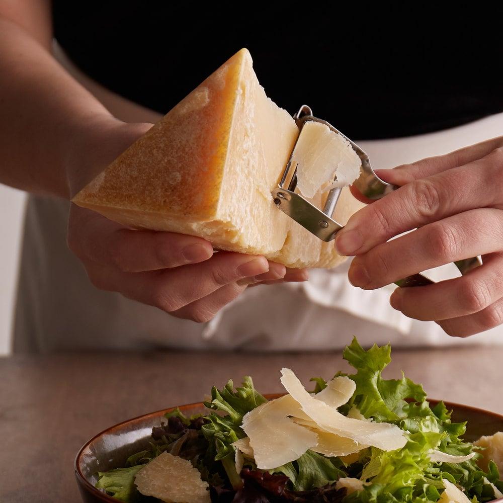 Person wearing a white apron slicing grana padano over a garden-fresh salad