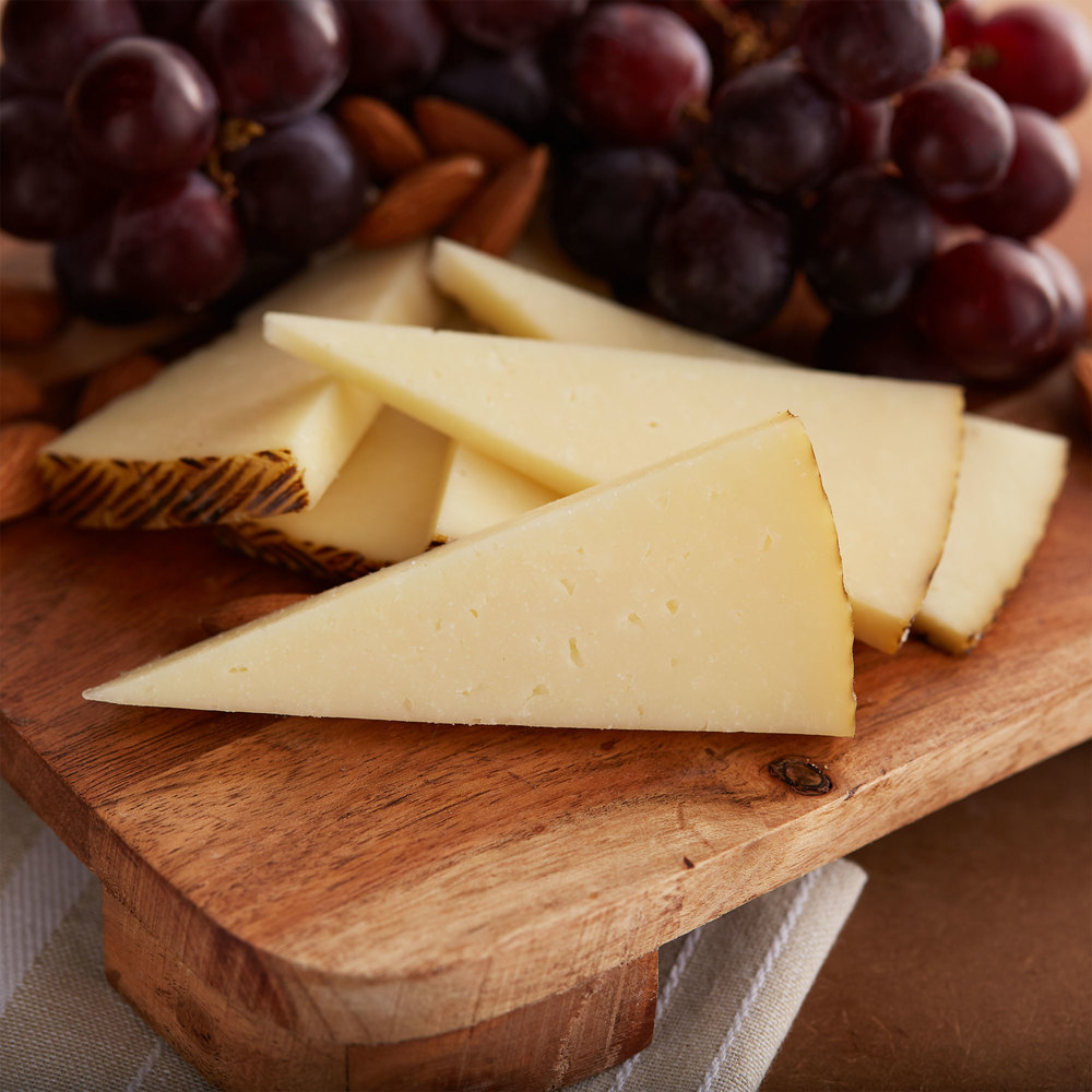 Slices of manchego on a wood serving board with red grapes in the background