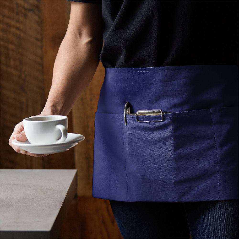 Chef in kitchen wearing a green cotton apron with brown leather accents