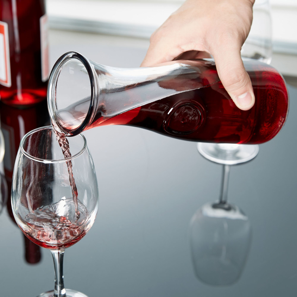 Carafe of wine pouring red wine into wine glass