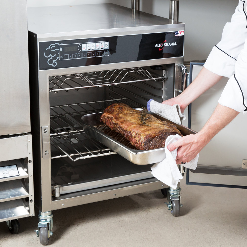 Arms pulling food pan filled with smoked meat from Alto-Shaam 767-SK/III undercounter unit