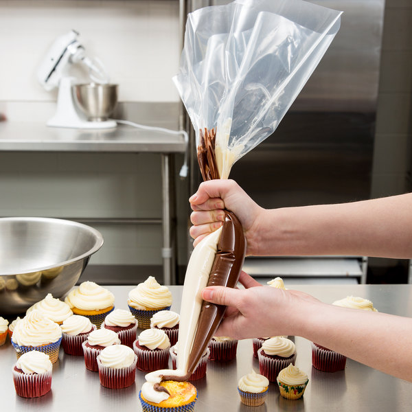 Baker decorating cupcake with a striping bag insert