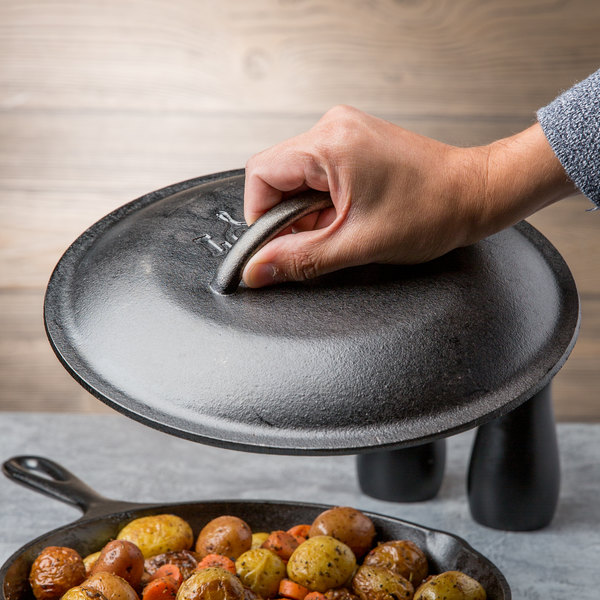 Man holding cast iron cover over cast iron skillet filled with roasted vegetables
