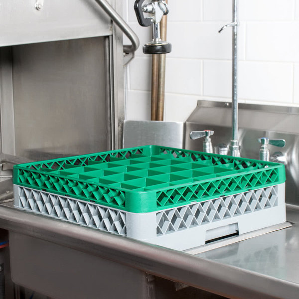 Gray plastic glass rack with green extender on commercial sink