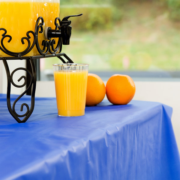 Cup of orange juice filled from a beverage dispenser sits on a bright blue disposable tablecloth