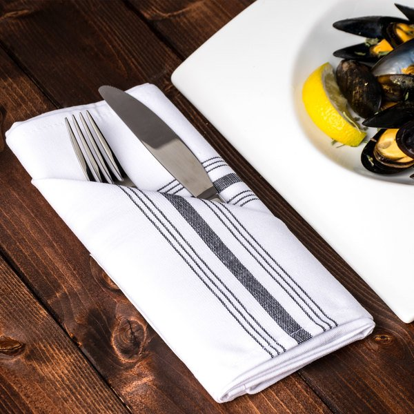 Folded white cloth napkin with black stripes holds a fork and knife on a wooden tabletop