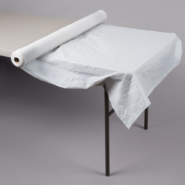 White plastic table cover roll drapes over one end of a rectangular folding table