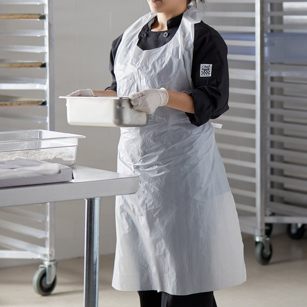 Employee carrying a stainless steel pan wearing a disposable plastic apron
