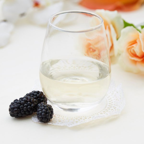 Stemless wine glass filled with white wine on an elegant table with roses in the background