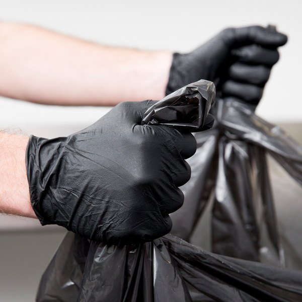 Holding a trash bag with powder-free gloves
