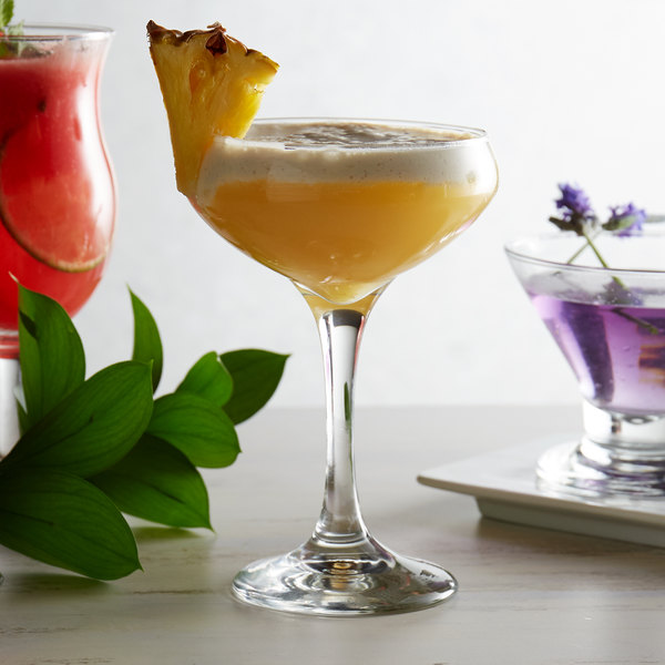 Coupe wine glass filled with a fruity drink, garnished with a slice of fresh pineapple