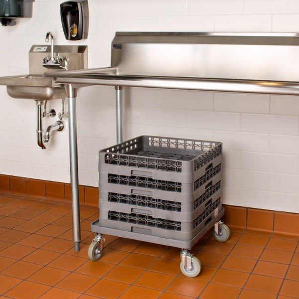 Four plastic glass racks on dolly underneath equipment table in commercial kitchen