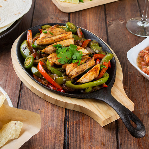 Cast iron skillet filled with grilled chicken and roasted vegetables
