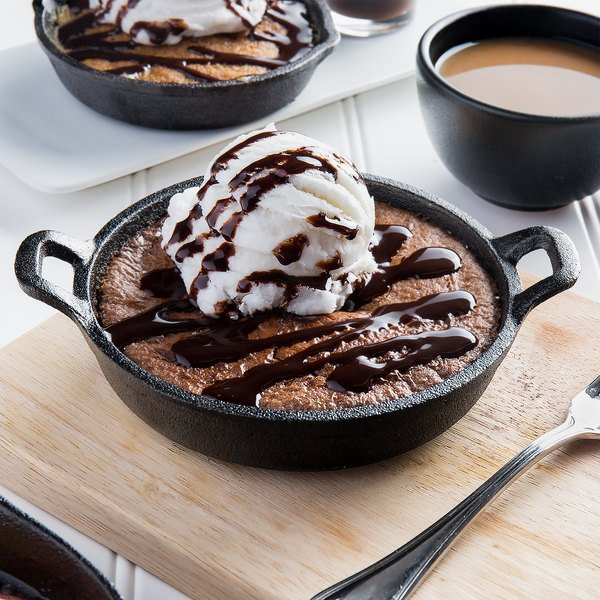 Cast iron casserole dish filled with brownie, topped with ice cream and drizzled with chocolate
