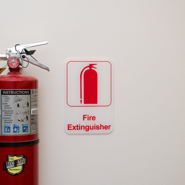 Fire extinguisher sign mounted on wall next to red Buckeye fire extinguisher