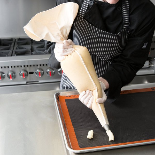 Baker holding a pastry bag filled with frosting