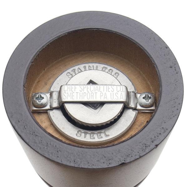 Bottom of dark wooden pepper / salt mill with stainless steel grinding mechanism