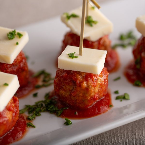 Provolone-topped meatballs on a white serving tray with a toothpick holding the appetizer together