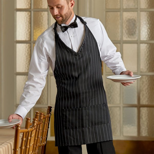Man removing dishes from table wearing a black and white pinstripe tuxedo apron