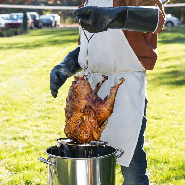 pulling a deep fried turkey out of a turkey fryer