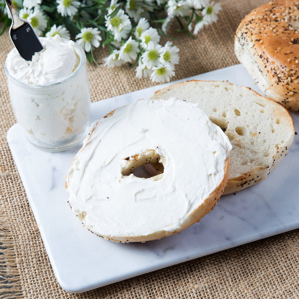 Everything bagel, sliced with cream cheese, on a marble serving board with flowers in the background