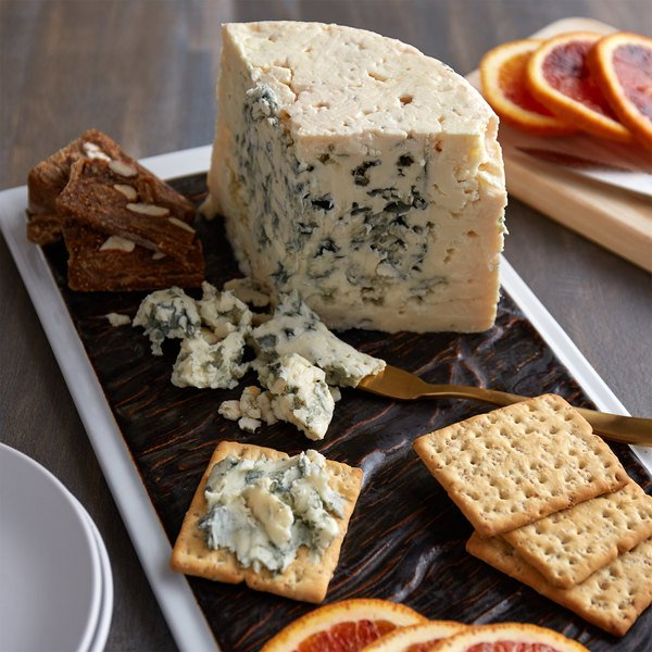 Wedge of roquefort on a serving board with crackers and slices of citrus fruit