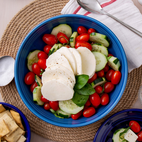 Sliced mozzarella cheese over a bed of cherry tomatoes, sliced cucumbers, and basil in a blue bowl