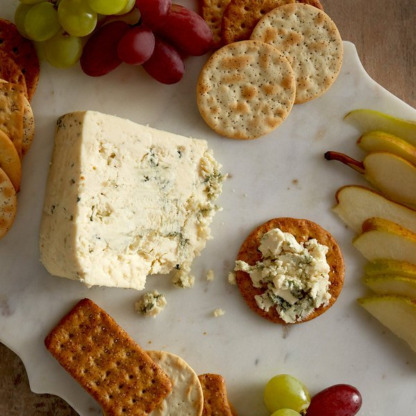 Wedge of gorgonzola on a marble charcuterie board with crackers, apples, and green and red grapes