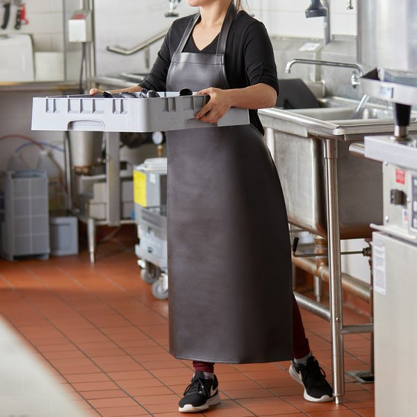 Chef moving rack of dishes in front of sink wearing a black vinyl apron