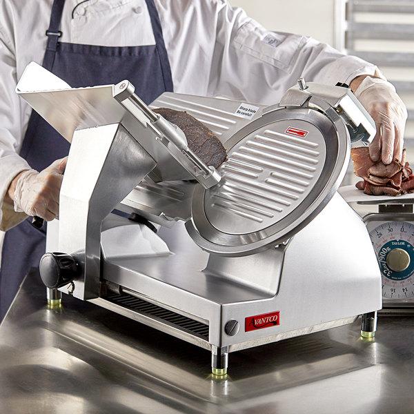 Worker using an Avantco mid tier slicer to slice roast beef