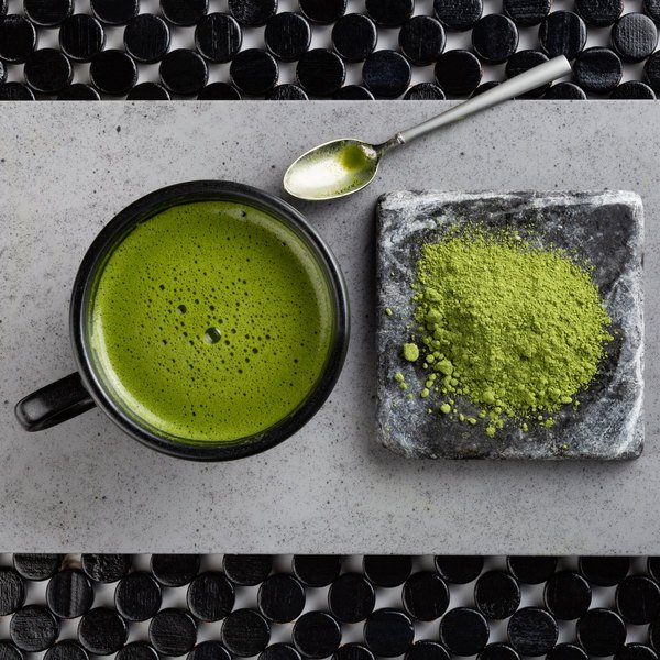 Cup of prepared matcha tea next to a plate of matcha tea powder