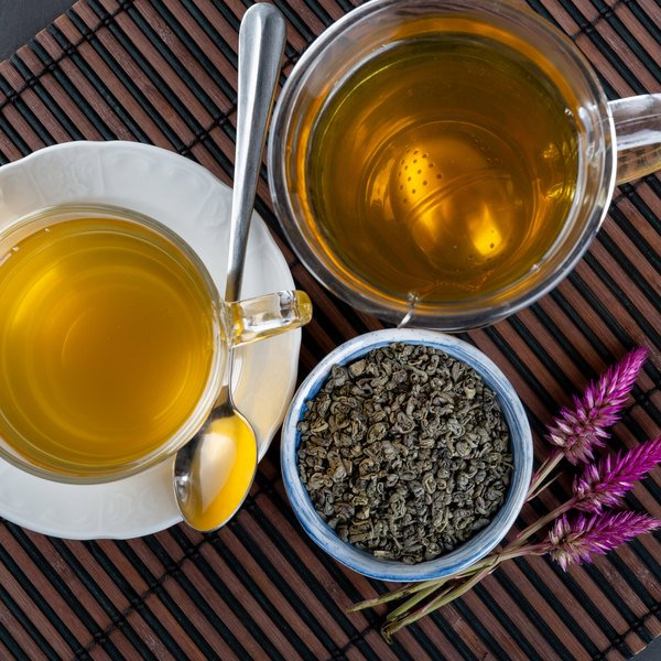 Two cups of tea next to a bowl of loose leaf tea