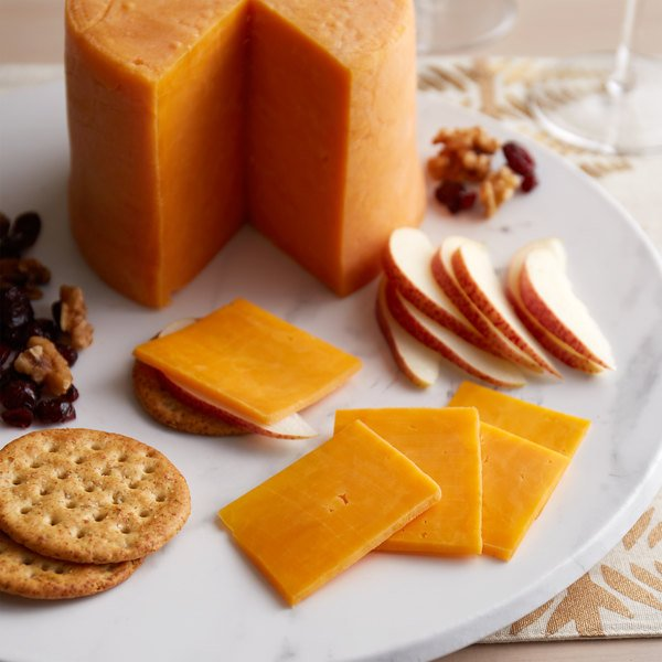 Round serving board with round of cheddar cheese, sliced cheddar cheese, crackers, apples, and nuts