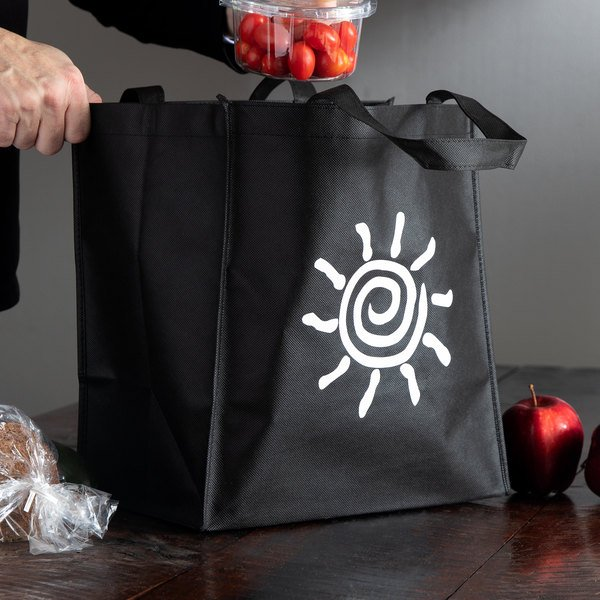 Black reusable canvas bag with white sun graphic with container of tomatoes being placed inside